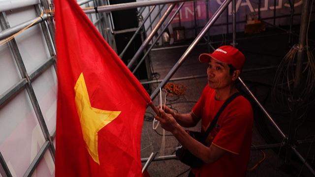 Một cổ động viên đang cố treo một lá cờ Việt Nam…