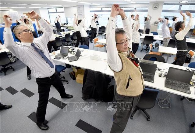 Nhân viên tập thể dục sau giờ nghỉ trưa tại một văn phòng ở thủ đô Tokyo, Nhật Bản. Ảnh: AFP/TTXVN