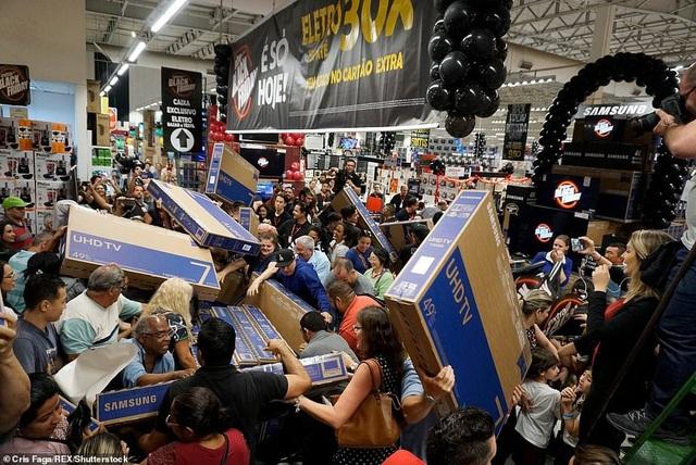 """Cơn sốt """"Thứ 6 đen tối"""" đã bắt đầu lan truyền trên khắp thế giới trong ngày 23/11. Đây là dịp để những người tiêu dùng có cơ hội được sở hữu các món đồ mong muốn với giá thành giảm rất mạnh. Vì vậy, rất nhiều khách hàng đã đổ xô tới các cửa hàng, siêu thị và bắt đầu công cuộc """"săn hàng giá rẻ"""". (Ảnh: Rex)"""
