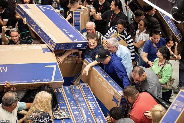 Để mua TV với giá giảm rất sâu, những khách hàng ở Sao Paulo, Brazil không ngần ngại việc phải chen lấn, xô đẩy, giành giật lẫn nhau. Khu vực siêu thị gần như không còn chỗ trống. (Ảnh: Rex)
