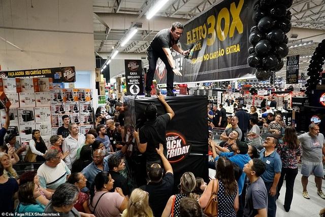 """Một nhân viên siêu thị ở Sao Paolo, Brazil đang cố gắng trấn tĩnh lại đám đông dường như đang """"vỡ òa"""" phía dưới. (Ảnh: Rex)"""