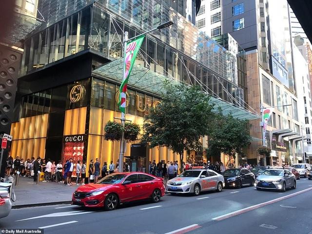 Nhân viên của thương hiệu thời trang Gucci phát nước uống cho những khách hàng đang kiên nhẫn chờ đợi trước cửa hiệu của hãng tại Sydney, Australia. (Ảnh: Dailymail)