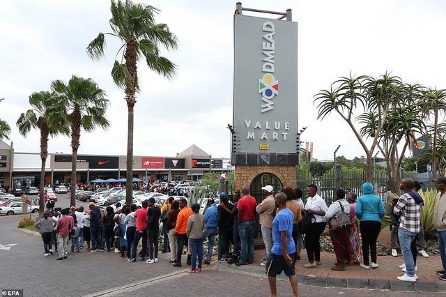 Dòng người nối đuôi nhau xếp hàng chờ đợi trước các cửa hiệu ở Johannesburg, Nam Phi. (Ảnh: EPA)
