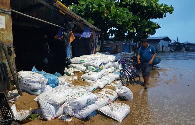 Lo ngại sóng biển lớn đưa nước vào nhà, người dân dùng bao cát để gia cố