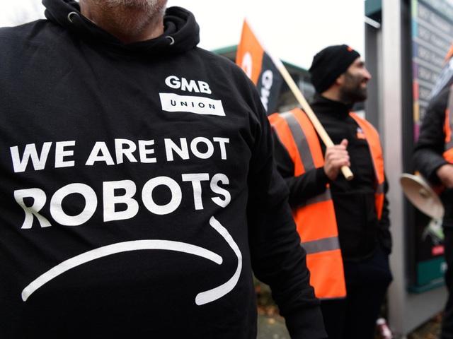 Dòng chữ: Chúng tôi không phải robot trên áo của người biểu tình tại các kho xưởng của Amazon.