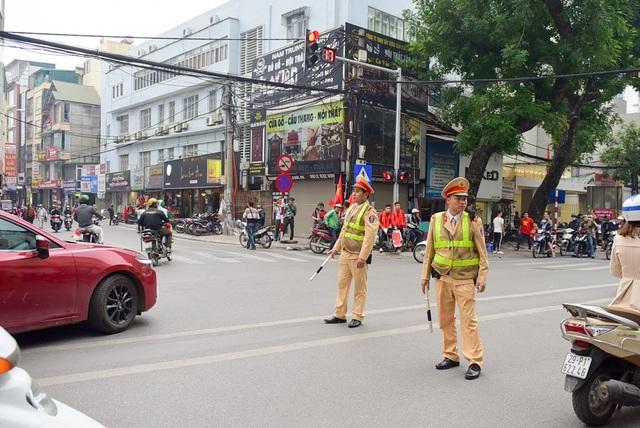 Phía bên ngoài sân có lực lượng cảnh sát giao thông điều tiết các phương tiện di chuyển qua khu vực đầu phố Trịnh Hoài Đức.