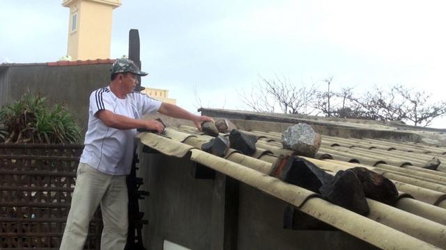 Chờ người mua bao cát về, ông Nam nhặt đá gia cố tạm lại mái nhà của mình