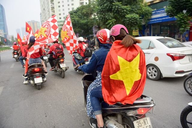 Một cổ động viên khoác trên vai lá quốc kỳ đi diễu hành cổ vũ cho đội tuyển nhà.