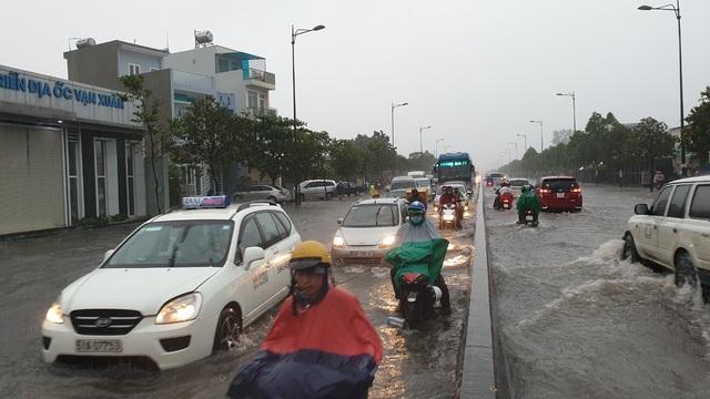 Ngập đến nửa xe máy trên đường Phạm Văn Đồng