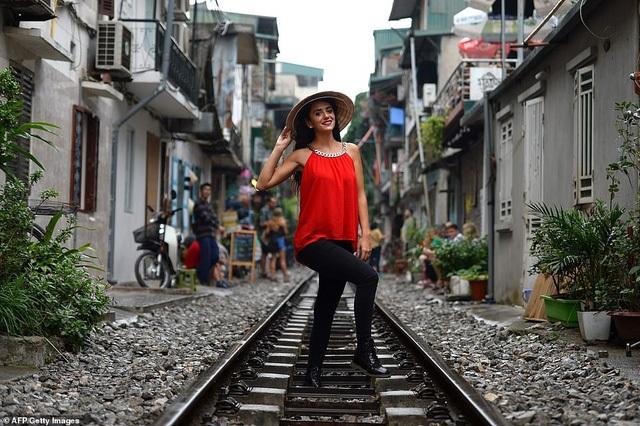 Một cô gái ngoại quốc đội nón lá, duyên dáng tạo hình trên đường ray