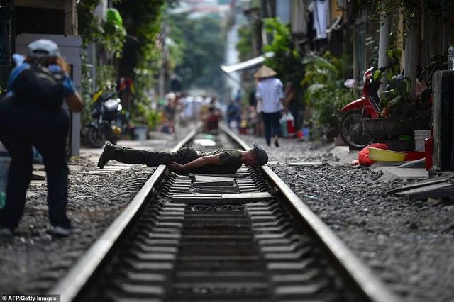 Một nam thanh niên tạo hình tư thế lạ để chụp ảnh trên đường ray