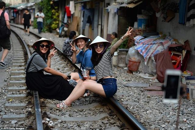 Nhóm các cô gái đội nón lá, ngồi trên đường ray để chụp hình