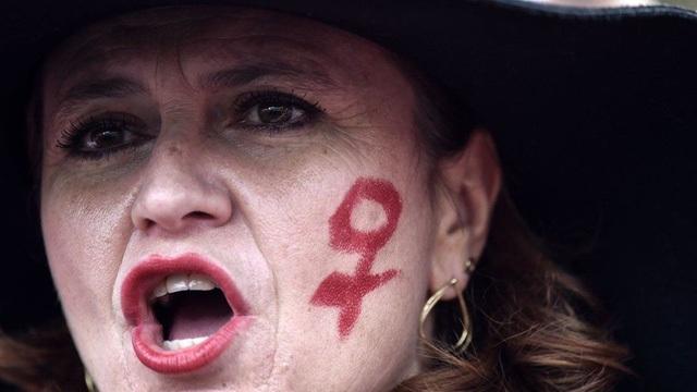 Một người tham gia tuần hành với biểu tượng nữ giới trên má tại Rome, Italy (Ảnh: AFP)