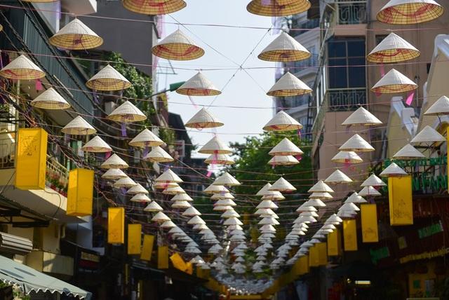 Diện mạo con phố thay đổi hẳn nhờ những chiếc nón lá được sắp đặt lạ mắt. Ngoài ra, dọc hai bên phố còn có rất nhiều đèn lồng.