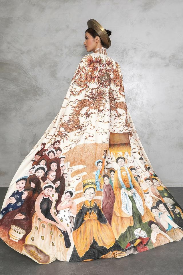 """Chất liệu bộ """"Hoàng bào"""" được may trên nền vải tafta sang trọng. Họa tiết nổi bật trong bộ """"Hoàng bào"""" này chính là hình ảnh """"Long phụng"""" bay lượn trên những tầng mây, miêu tả hình ảnh vừa cao quý, vừa mang tính hòa hợp. Phần dưới là hình ảnh tầng tầng, lớp lớp con người sống sung túc, tượng trưng cho """"con rồng cháu tiên"""" thể hiện sự hưng thịnh, đoàn kết các dân tộc anh em trong đời sống của Việt Nam thông qua bức tranh được vẽ sơn mài tinh tế."""