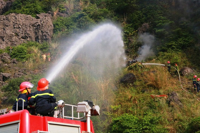 Hai xe chữa cháy của lực lượng cứu hỏa cũng nhanh chóng được điều động đến hiện trường dùng vùi phun công suất lớn phun nước lên núi dập lửa.