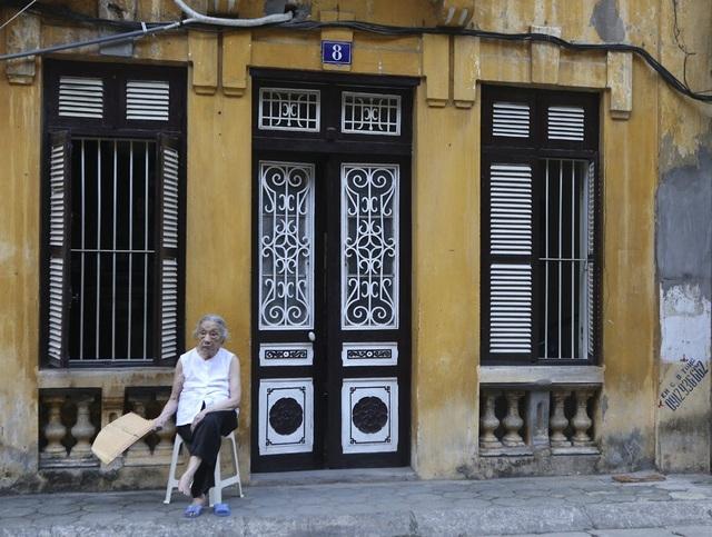 Một cụ già ngồi thư giãn trước căn nhà cổ phố Phan Huy Ích.