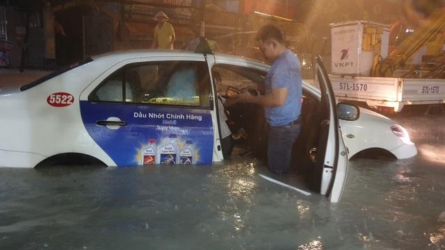 Một đoàn khách di chuyển trên taxi phải xuống xe lội bộ vì nước ngập hết nửa xe không thể di chuyển.