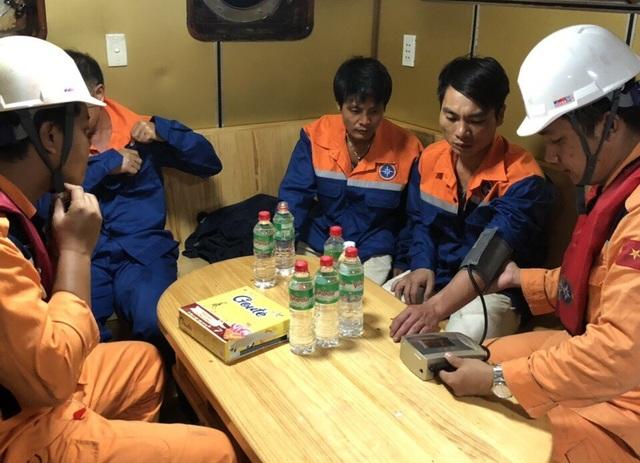Lực lượng chức năng làm việc với các thuyền viên tàu hàng sau khi giải cứu tàu này bị va phải bãi đá ngầm