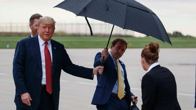 Tổng thống Donald Trump cầm ô từ tay trợ lý Jordan Karem. (Ảnh: AP)