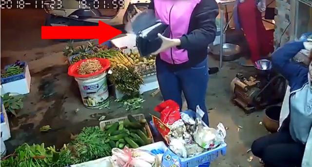 Vị khách mua hàng nhanh tay kẹp tờ tiền mệnh giá 20 ngàn đồng vào ngón tay của tay cầm ví.