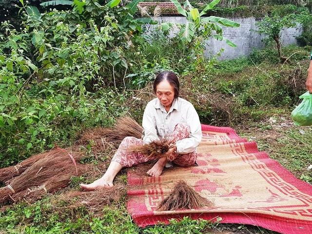 Một người dân mang cả chổi ra ngồi bện bên đường để túc trực phản đối dự án.