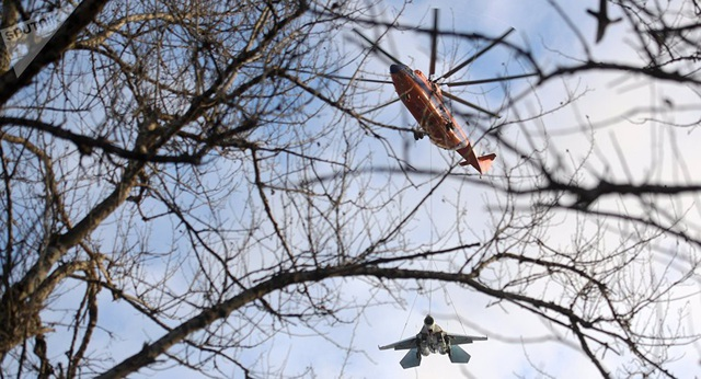 Trực thăng quân sự Nga treo lơ lửng máy bay chiến đấu Su-27 trên trời (Ảnh: Sputnik)