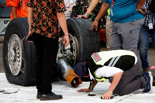 Các nhân viên kỹ thuật kiểm tra phần bánh máy bay vớt được từ dưới biển.