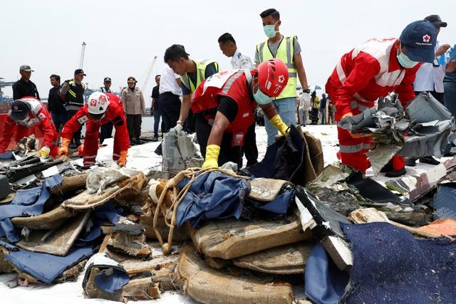 Các nhân viên cứu hộ kiểm tra các vật dụng được vớt lên cảng Tanjung Priok ở Jakarta.