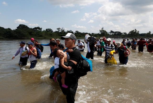 Các gia đình bế theo con nhỏ vượt qua sông ở biên giới Mexico - Guatemala trước khi di cư tới Mỹ.