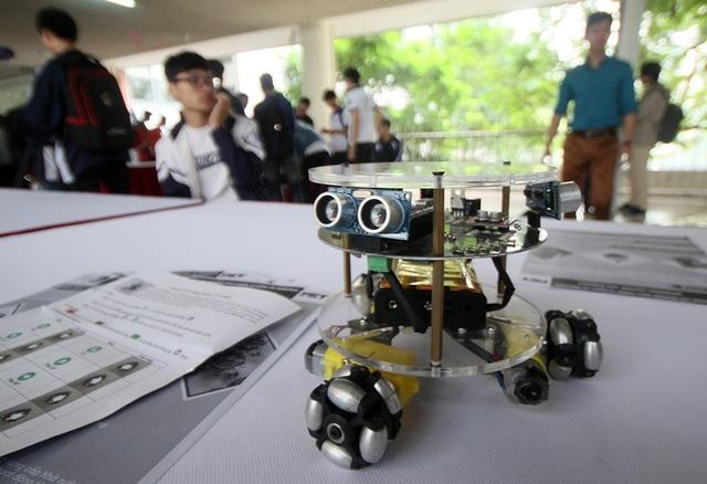 Trong ảnh là mẫu robot UET R01 được giới thiệu tại ngày hội Toán học mở 2018. Robot này là loại robot di động được nhóm sinh viên năm 4, trường Đại học Công nghệ thiết kế, chế tạo tại Phòng thí nghiệm Điều khiển tự động và Robotic. UET - 01 sử dụng bộ điều khiển Aduino Nano, có khả năng thay đổi hướng chuyển động theo hướng tùy ý mà không cần thực hiện các động tác xoay, có thể kết nối, điều khiển từ điện thoại thông minh qua Bluetooth, có khả năng tự tránh vật cản nhờ sử dụng 3 cảm biến siêu âm.