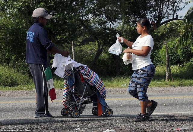 Một phụ nữ địa phương tiếp nước uống và lương thực cho hai cha con ở bang Oaxaca - Mexico. Ảnh: AP