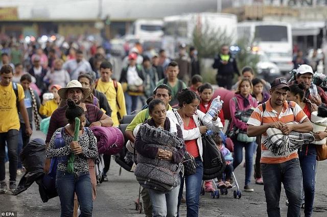 Đoàn người di cư mang theo hành lý đến nơi tạm trú ở một nhà thờ thuộc TP Puebla - Mexico. Ảnh: EPA