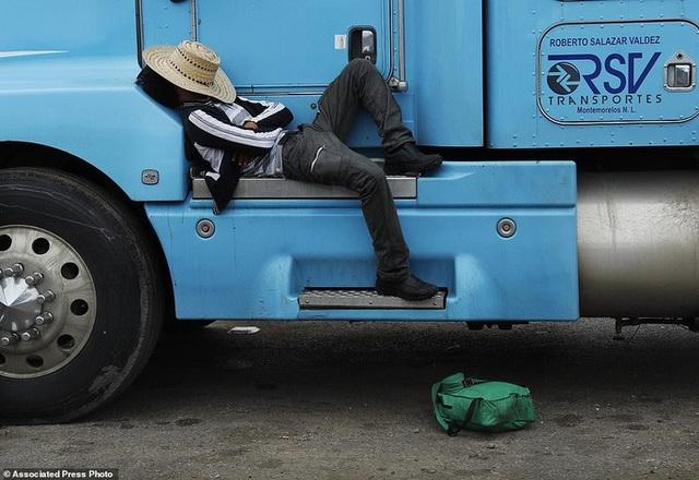 Một người di cư tranh thủ chợp mắt sau quãng đường dài di chuyển. Ảnh: AP