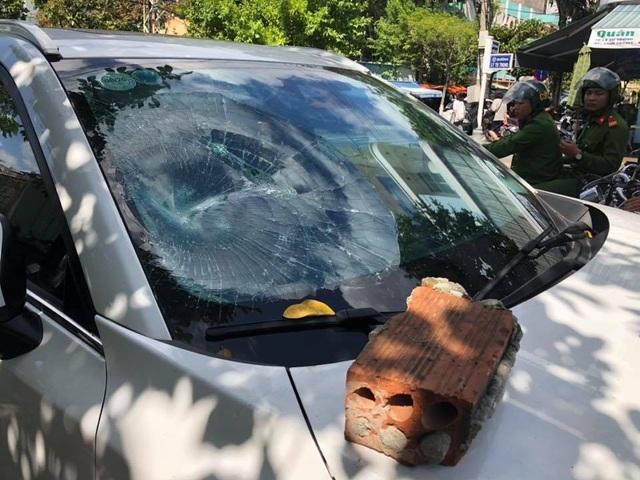 Ô tô bị đập vỡ nát kính trước và đèn xe. Hung khí là một viên gạch lớn.