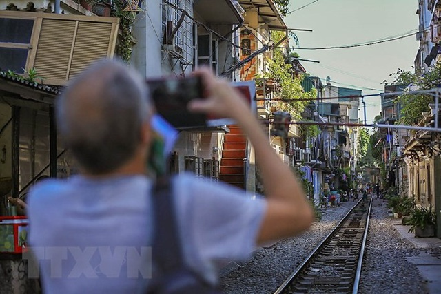 Du khách thích thú ghi lại những hình ảnh của phố đường tàu khi ghé đến nơi đây. (Ảnh: Trọng Đạt/TTXVN).