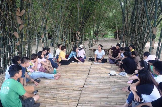 Đoàn du khách ngồi bàn bạc công việc dưới tán luỹ tre làng mát rười rượi.