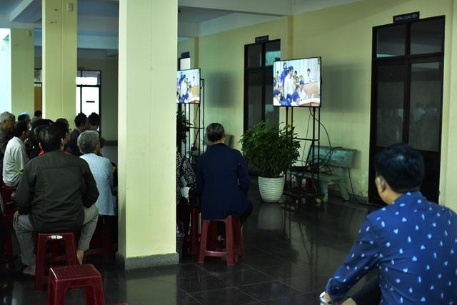 Những người dân không có thư mời ngồi ngoài theo dõi cuộc gặp gỡ qua màn hình ti vi