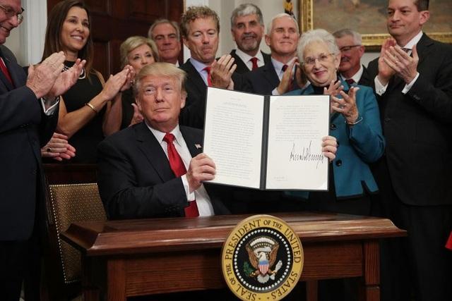 Tổng thống Trump ký sắc lệnh hành pháp. (Ảnh: Reuters