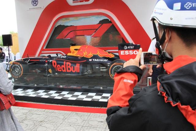 Chiếc xe đua F1 được trưng bày ngay trên vỉa hè đường Hoàng Diệu, phía trước lối vào Hoàng Thành Thăng Long (Hà Nội) đã thu hút rất nhiều người dân đến chụp ảnh kỉ niệm trong sáng nay 8/11.