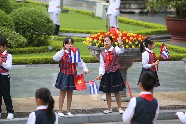 Các cháu thiếu nhi Việt Nam cầm cờ chào đón lãnh đạo Cuba tới thăm