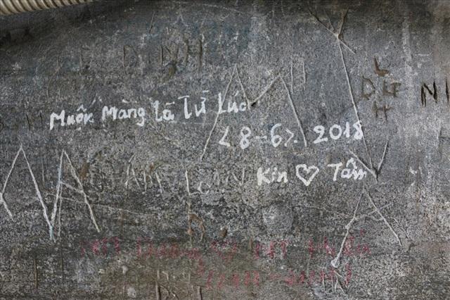 Những dòng chữ bằng bút xoá, những vết khắc bằng đá trên bề mặt môt di tích ở Hà Nội. Ảnh Tùng Nguyễn.