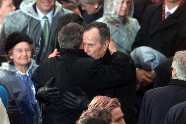 """Cựu Tổng thống George H.W. Bush ôm con trai George W. Bush sau khi Bush """"con"""" tuyên thệ nhậm chức năm 2001. Họ là cặp cha con tổng thống thứ 2 trong lịch sử Mỹ. (Ảnh: AFP)"""