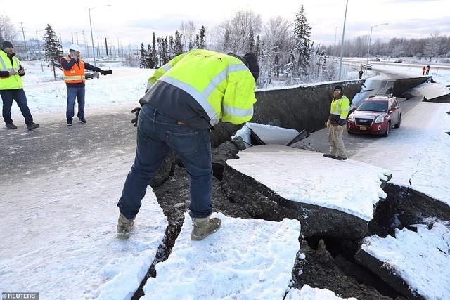 Một chiếc xe bị kẹt và lún xuống đoạn đường đã bị động đất làm nứt gẫy nghiêm trọng (Ảnh: Reuters)