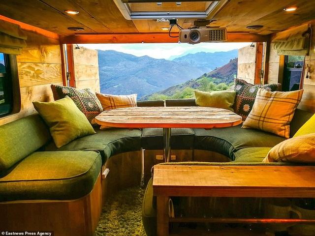 Guy Williams đã mua một chiếc xe vốn dùng để chở ngựa, rồi thay mới, lắp ghép nhiều chi tiết, biến xe chở ngựa trở thành nhà di động xinh xắn. Trong ảnh là không gian phòng khách kiêm phòng ăn với chất liệu gỗ ấm áp, mộc mạc và một khung cửa sổ có thể mở ra những góc nhìn tuyệt đẹp.