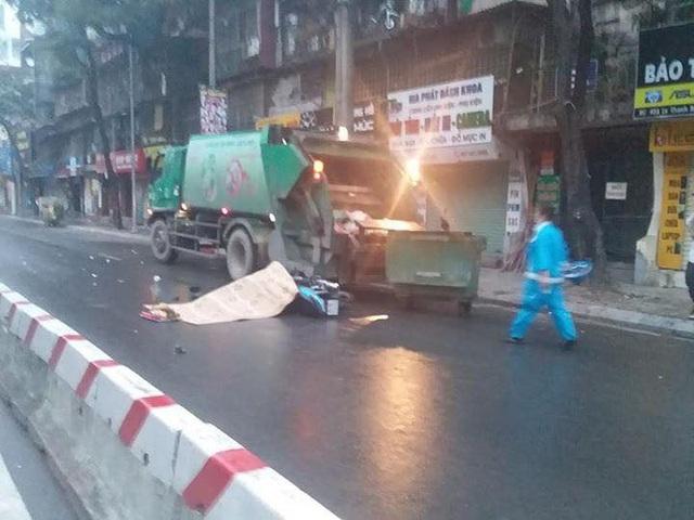 Chiếc xe chở rác đỗ bên đường trong đêm mưa. (Ảnh: Lê Phương).
