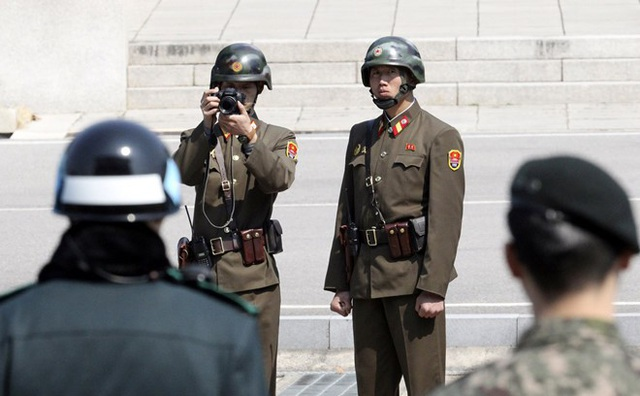 Binh sĩ Triều Tiên đưa máy ảnh về phía binh sĩ Hàn Quốc tại khu vực an ninh hỗn hợp ở Khu phi quân sự liên triều. (Ảnh minh họa: Japan Times)