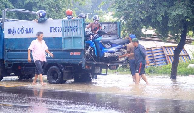 Xe tải chở xe máy qua đoạn nước ngập sâu, người dân phải trả 30.000 - 50.000 đồng/xe máy.