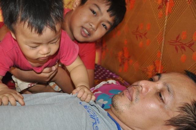 Cô bé Thủy (1 tuổi) và anh trai lớn (lớp 4) trông bố để mẹ đi tìm bé Đại Nghĩa (4 tuổi).