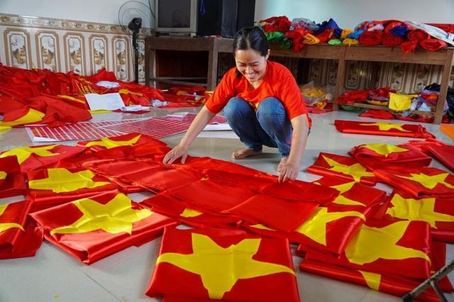 Cơ sở của chị Vương Thị Nhung ở thôn Từ Vân (xã Lê Lợi) chuyên làm cờ Tổ quốc và các loại băng rôn, cờ vẫy, áo cờ đỏ sao vàng ... những ngày gần đây tất bật cả ngày lẫn đêm, huy động nhiều nhân công làm việc để phục vụ nhu cầu của người hâm mộ bóng đá khắp cả nước.